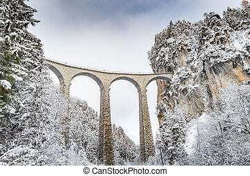 The Landwasser Viaduct with Railway without famous train at winter, landmark of Switzerland, snowing, river and mountains