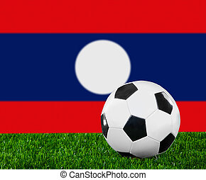 The Laotian flag and soccer ball on the green grass.