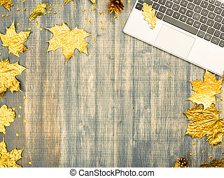 The Laptop keyboard and golden maple leaves.