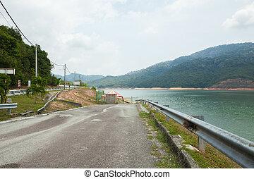 the largest dam in Penang, Malaysia. - Road on dam ridge in...