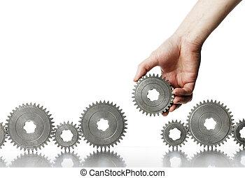 Man adding a cog gear wheel to a row.