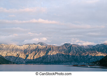 The last rays of the sun at the top of the mountain. Rocky mountains over the city of Dobrota, in Kotor Bay, Montenegro.