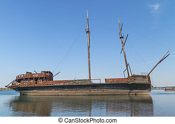 On one of the lakes in Ontario, on the dock, a rusting three-masted ship is living out its last days.
