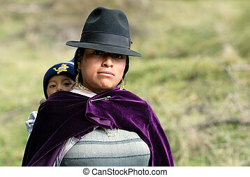 the latin woman in national clothes with little child. ...
