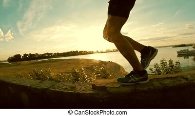 The legs of a man runner - have jogging in park at sunset, close-up, slow-motion