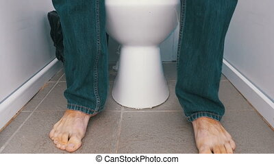 The Legs of a Man Sitting and Stand up from Toilet. A man in...