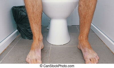 The Legs of a Man Sitting and Stand up from a Public Toilet....