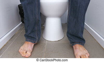 The Legs of a Man Sitting and Stand up from a Public Toilet