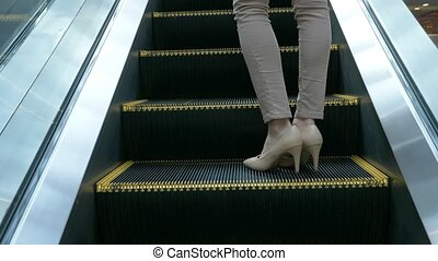 The legs of a woman in beige trousers, in beige shoes standing on a moving escalator