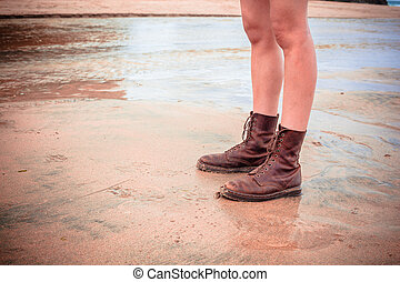 The legs of a woman standing on the beach