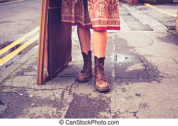 The legs of a young woman standing in the street with...
