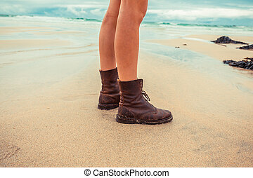The legs of a young woman standing on beach