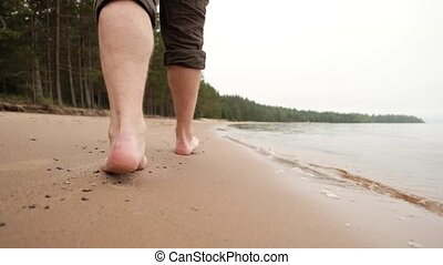 The legs of caucasian man going on sand near water