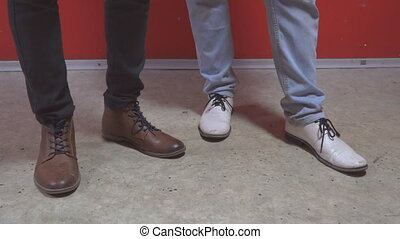 The legs of two men in shoes. Boots of white and brown...