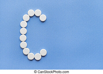 The letter C vitamin is lined with white tablets on a blue background.