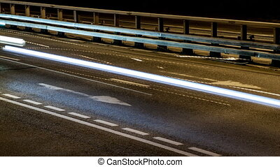 The light of car headlights on the road, night timelapse