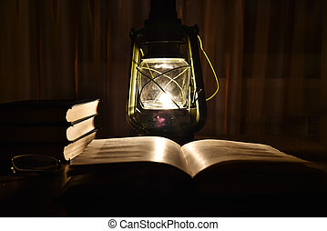 The light of kerosene lamp and open book on the table - The...