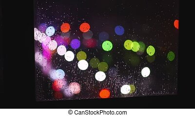 The lights of city life and drops of water are reflected on ...