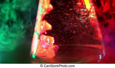 The liquid is boiling in flask in neon color light....
