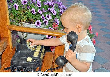 the little blonde boy talks on a vintage telephone