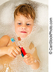 The little boy bathes in a bathroom