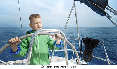 The little boy drives a sailing yacht in caribbean sea
