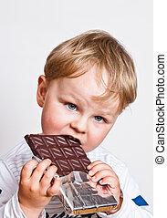 The little boy eats chocolate