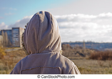 The little boy in a jacket costs a back on the nature in the autumn and looks at a city in the distance