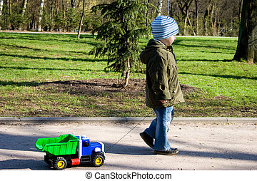 The little boy is playing with car.