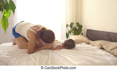 little boy is playing with his mother on the bed laughing fun