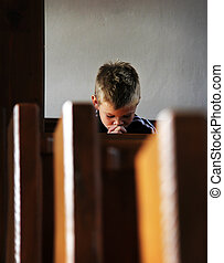 the little boy is praying in the church