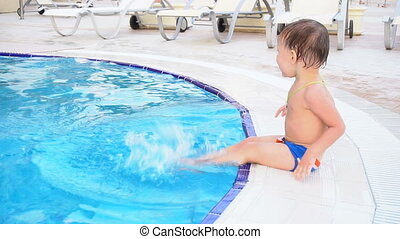the little boy is sitting poolside at the resort