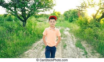 the little boy is walking on a dirt road