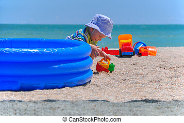 the little boy plays toys in sand on the beach