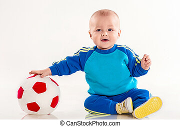 the little boy plays with a ball