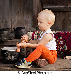 The little boy plays with a doll