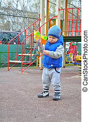 the little boy plays with a toy at the playground