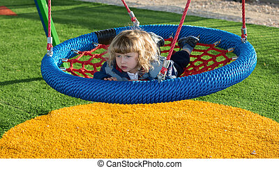 The little boy shakes on swing