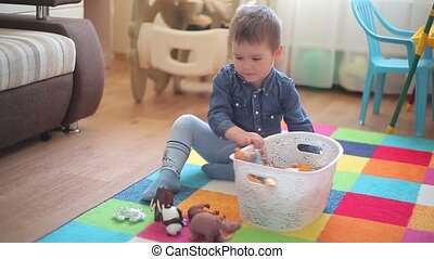 The little boy sits on the floor and plays with various animals