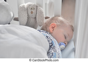 the little boy sleeps with a pacifier