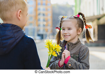 the little gentleman gives the girl a bunch of flowers