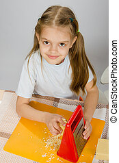 The little girl at the table t grated cheese