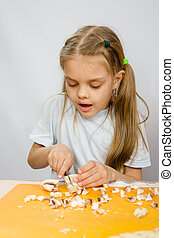 The little girl at the table with diligence knife cutting mushrooms