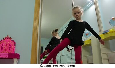 The Little Girl Ballerina Stretches Poses - Little girl...