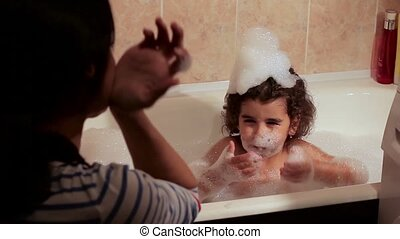 The little girl bathes in a bath with foam. foam hit in the mouth. Discontent. Rinsing the mouth with water