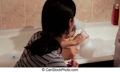 The little girl bathes in a bath with foam. She laughs, has fun with her mother.