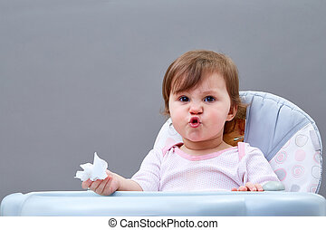 The little girl blows her nose into a paper handkerchief on grey background