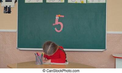the little girl draws something