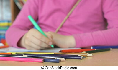 The little girl draws the pictures in the copybook