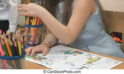 The little girl draws the pictures in the copybook - The...